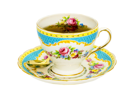 Antique fine china tea cup and saucer with tea isolated on white.