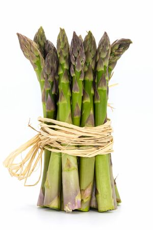 Bunch of fresh green asparagus close-up isolated on white.