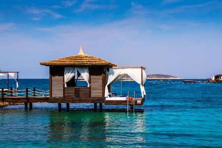 Beach cabana on a wooden pier.
