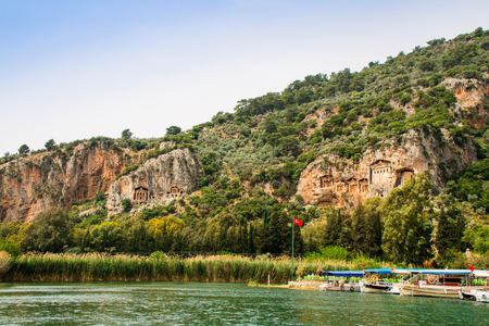 River Dalyan in Turkey with the sheer cliffs and the weathered facades of Lycian tombs cut from rock, circa 400 BC.