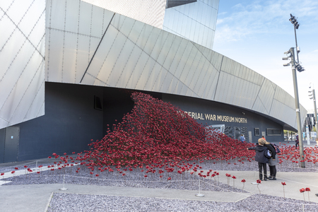 MANCHESTER, UK - September 25, 2018: The iconic red poppy sculpture Wave by artist Paul Cummins and designer Tom Piper outside the IWM North. Editorial