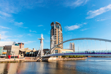 MANCHESTER, UK - September 25, 2018: Modern buildings at Salford Quays with vertical lift Millennium Footbridge.