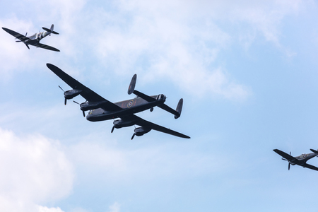SADDLEWORTH, UK - August 6, 2016: Lancaster Bomber and two Spitfire planes formation memorial flight at WW2 day. Editorial