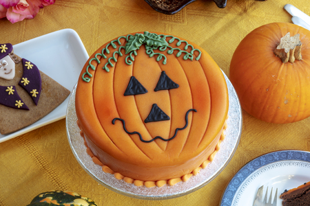 Novelty cake decorated with marzipan and icing in Halloween pumpkin theme. 免版税图像