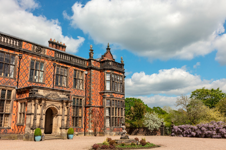 Historic English stately home, built in red brick, and surrounding park.