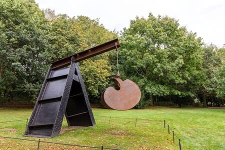WAKEFIELD, YORKSHIRE, UK - October 19, 2019:  The Cave, an abstract steel sculpture by Mark di Suvero in rural surroundings of Yorkshire Sculpture Park.