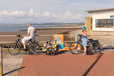 Morecambe, UK - July 19, 2021: Mature cyclist couple with luxury doggy trailer carrying two happy terrier dogs at the seafront in Morecambe. Publikacyjne