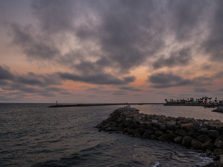 Red sky with sunset behind breakwater