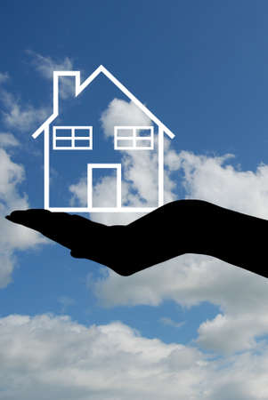 hands holding house: hand silhouette holding a house with sky in background Stock Photo