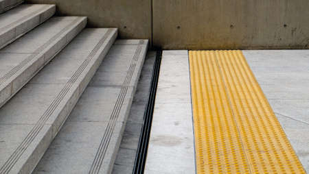 impaired: Concrete Stairs top with Grey Granite which has anti-slip groove and steel gutter cover at the bottom. And yellow Tactile paving to assist pedestrians who are blind or visually impaired. Stock Photo