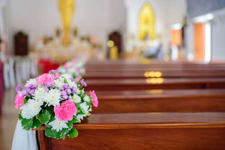Colorful flowers are placed on the church bench for weddings.