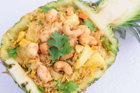 Tropical style pineapple firerice serving in pineapple peel topping with shrimp and cashew nut. Stock Photo