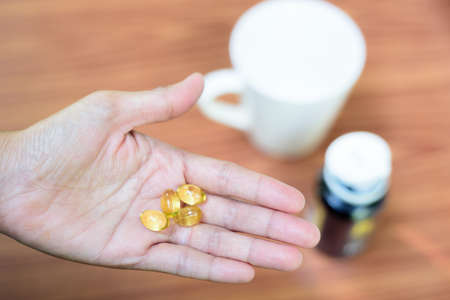 Many vitamins nourish the body, placed on the hands, see the medicine bottle far away.