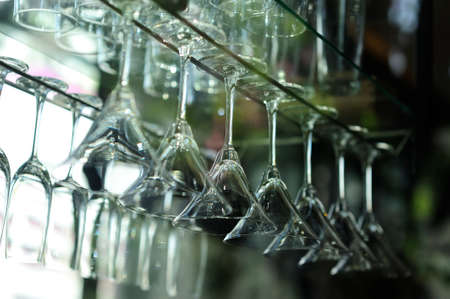 A glass of wine hanging on a bar of beverages.
