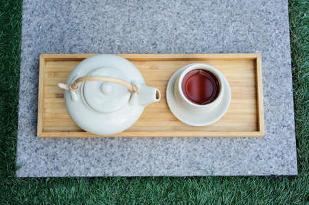 Hot tea is in the cup. Placed on a wooden tray. For a moment of rest of the day.