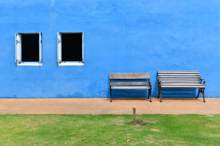 Wooden chairs are located beside the window. There is a blue cement wall on the background.