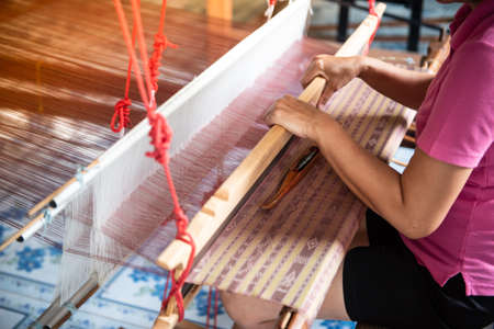 The woman's hand is intentionally weaving silk. Stock Photo