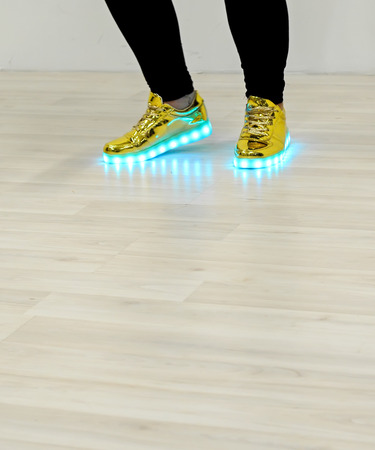 Fashionable sneakers with LED lighting on the legs of a girl Imagens