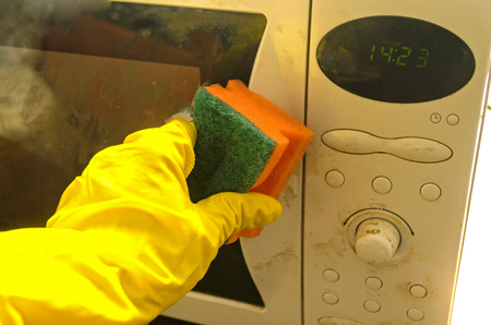 Hand washes the front surface of the microwave oven with a damp sponge