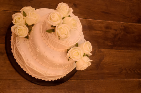 fake cake with flowers on wooden background.
