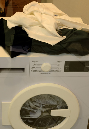 washing machine and dirty linen on it Imagens