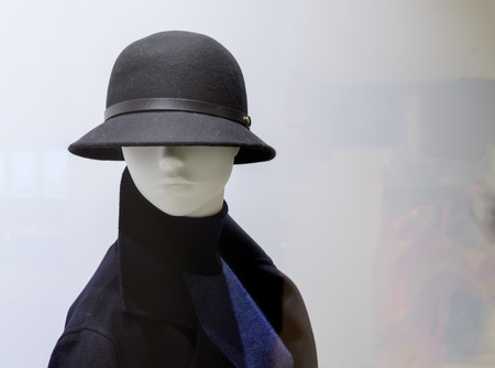 Female mannequin in a fashion hat on light background.