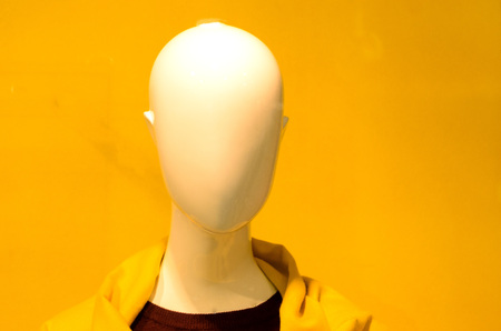 a mannequin head in a yellow jacket on a yellow background