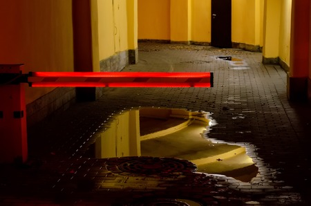 the barrier with red neon light closes the entrance in the parking house.