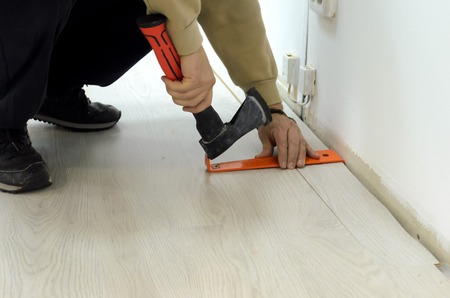 Renovation of an apartment, man laying laminate flooring in the room. Imagens