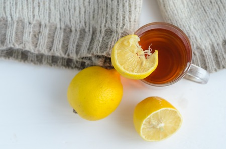 cup of tea with lemon , one and half lemon and woolen sweater. Imagens