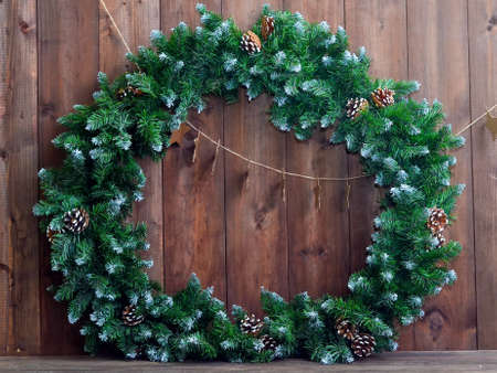 great Christmas wreath with pine cones on a wooden background.