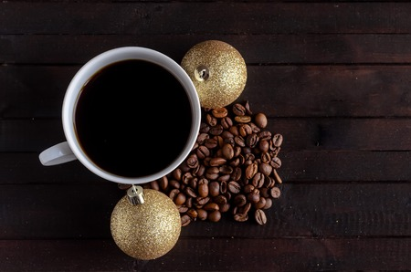 Cup of coffee with coffee beans and two Christmas balls.Christmas concept. Imagens