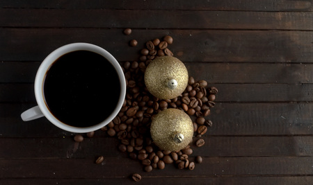 Cup of coffee with coffee beans and two pair Christmas golden balls.Christmas concept.
