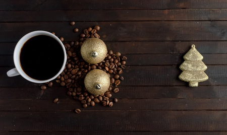 Cup of coffee with coffee beans ,two pair Christmas golden balls and toy Christmas tree .Christmas concept.