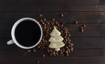 Cup of coffee with coffee beans and toy Christmas tree .Christmas concept.