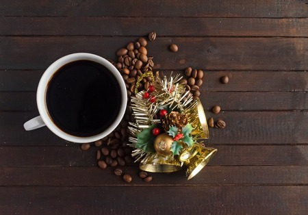 A cup of coffee, coffee beans and Christmas toy with three golden bells. Imagens
