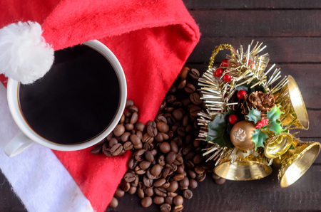 A cup of coffee,coffee beans ,Santa hat,and Christmas toy with three golden bells.Christmas concept.