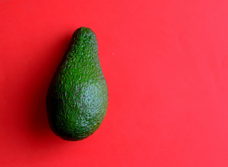 Green avocado on a red background. Healthy diet fruit.