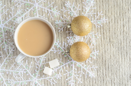 A Cup of coffee with milk, two pieces of sugar ,decorated snowflakes and two pair Christmas golden balls on a light wool sweater.Winter concept. Imagens