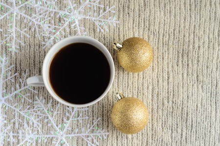 A Cup of coffee , decorated snowflakes and two pair Christmas golden ballson a light wool sweater.Winter concept.