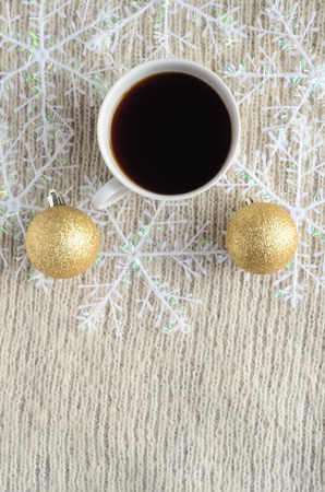 A Cup of coffee , decorated snowflakes and two pair Christmas golden balls on a light wool sweater.Winter concept.Vertical view.
