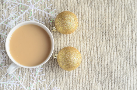 A Cup of coffee with milk,decorated snowflakes and two pair Christmas golden balls on a light wool sweater.Winter concept.