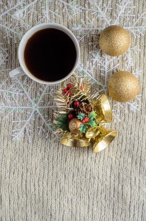 A Cup of coffee ,decorated snowflakes and Christmas toy on a light wool sweater.Winter concept.Vertical view.