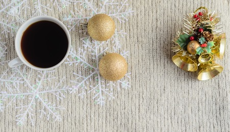 A Cup of coffee ,decorated snowflakes, two pair Christmas golden balls and Christmas toy on a light wool sweater.Winter concept.