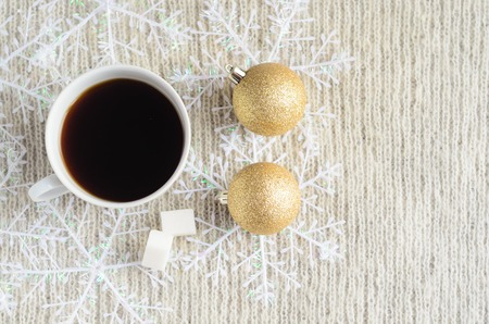 A Cup of coffee , decorated snowflakes and two pair Christmas golden balls on a light wool sweater.Winter concept.