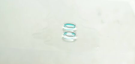 Panorama of Two contact lenses on white glass background.Focus on front lense.