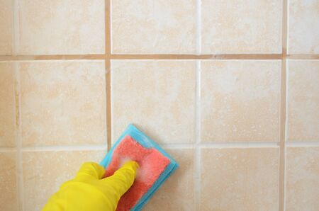 hand in yellow protective glove with sponge washes ceramic tiles with washing foam . Early spring cleaning or regular clean up.Space for text on top Banque d'images - 129619084