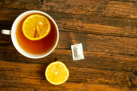 Top view, a cup of tea with lemon, a half of lemon and one pill on wooden background, copyspace.
