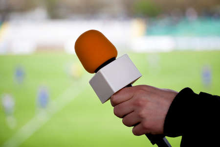 hand hold microphone for  interview during a football mach photo