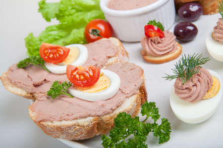 plate with slices of bread with pate and tomatoes and eggs